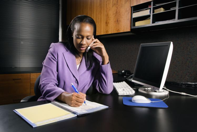 African-American young adult business woman talking on cell phone and writing in planner in office.